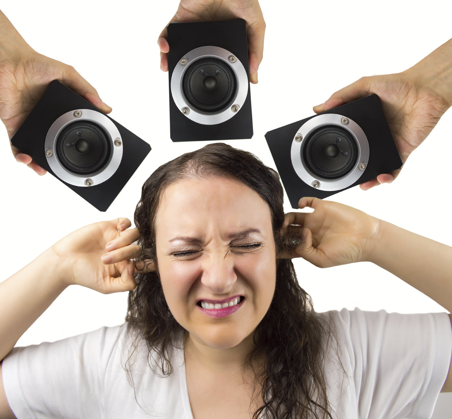 woman with hands in the ears disturbed by loud noise of the speakers