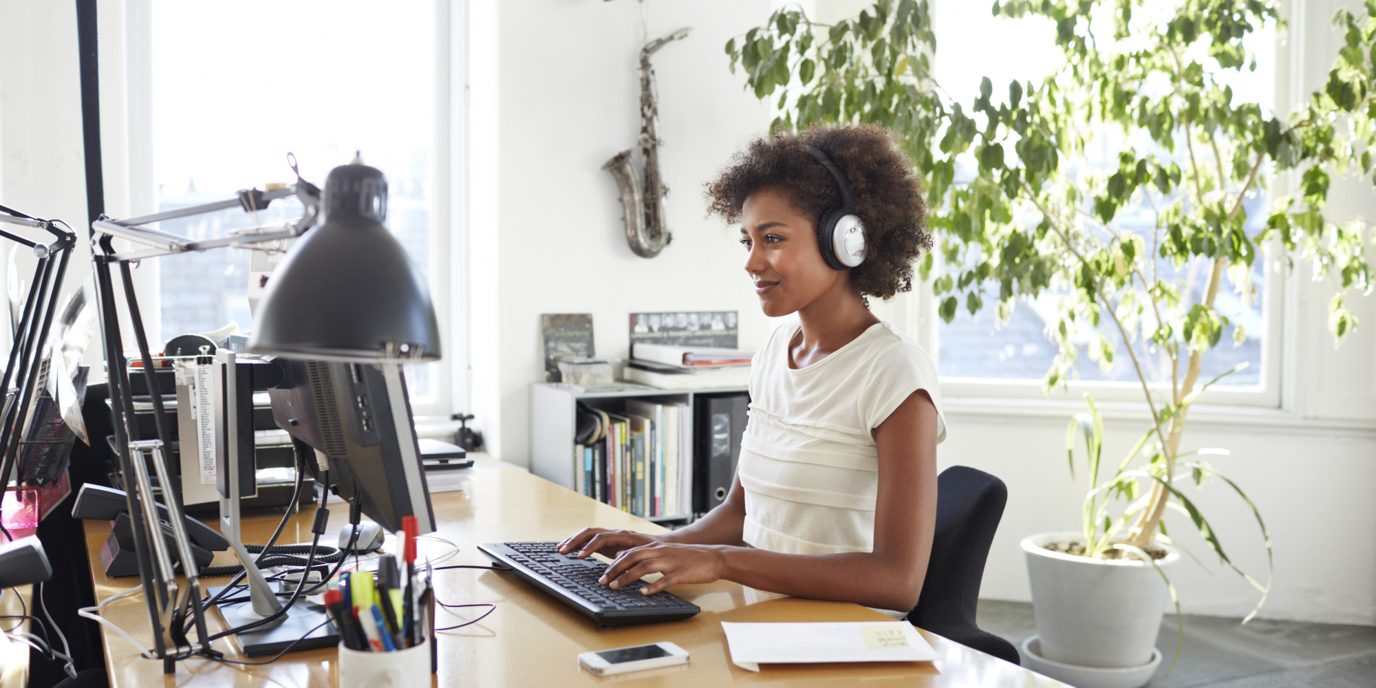 Businesswoman with headphones typing on keyboard